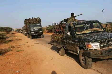 Trucks carrying Somalia troops with guns.