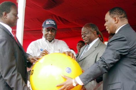 Former Minister for Information Samuel Poghisio (left) and former Permanent Secretary Dr. Bitange Ndemo (right) hold a huge buoy as President Kibaki (second right) looks on, and Prime Minister Raila Odinga (second left) at the Fort Jesus sea front on June, 12 2009.