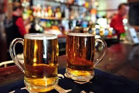 Two mugs of beer in a bar.