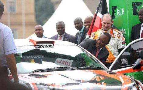 President Uhuru Kenyatta enters a rally car driven by Ian Dancun during the KCB Safari Rally flagging off ceremony at KICC Nairobi, on September 21, 2014.