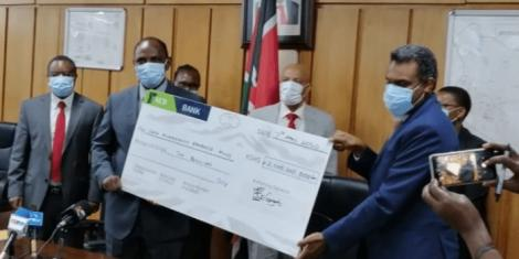 DPP Noordin Haji (right) presents a Ksh.2 billion dummy cheque to Treasury CS Ukur Yatani on April 7, 2020