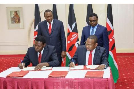 Governor Mike Mbuvi Sonko and Devolution CS Eugene Wamalwa signing an agreement in State House on Tuesday, February 25.