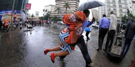 A man helps a woman cross flooded street in Nairobi