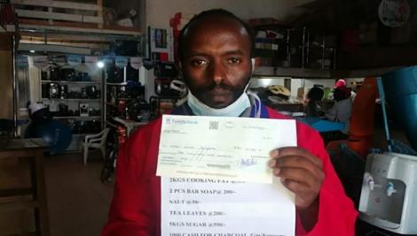 Wanjohi Ndungu poses for a photo with the cheque addressed to the president on Apil 4, 2020.