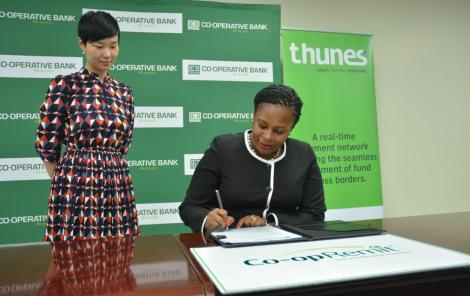 Head of Diaspora Banking at Co-op Bank Pauline Kieme signs-off the launch Co-opRemit, as the Senior Vice President - Africa at Thunes Ms Sandra Yao looks on.