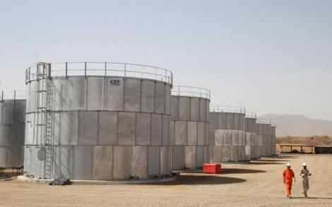 Workers walk past storage tanks at Tullow Oil's Ngamia 8 drilling site in Lokichar, Turkana County.