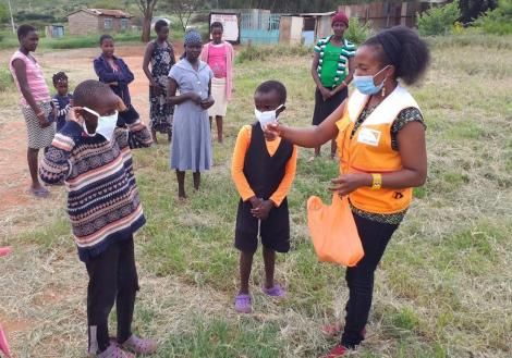 A volunteer hands over masks to children in Kajiado County in May 2020