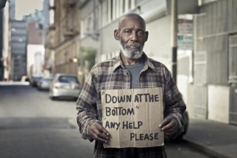 A man holding up a sign asking strangers for help.