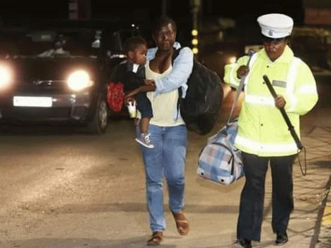 Amina Ramadhan, a police officer from Embakasi assisting an overwhelmed mother who was stranded on the first night of the curfew on March 27.