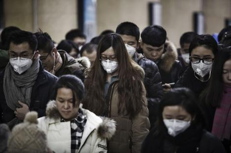 A photo of Passengers wearing face masks walk through a subway station in Beijing, China, on January 6, 2020.