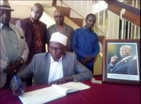 The famous inter-parties parliamentary (IPPG) chairperson J.J Falana of 1997, who was then the MP for Saku inscribes a message of condolence at the County commissioner's office in Marsabit. Looking on is a former assistant minister for information and broadcasting Elisha Godana (in a hat).