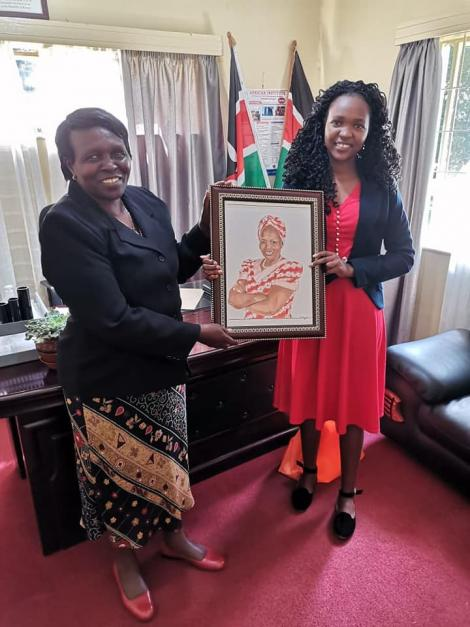 Pencil artist Ruth Muge giting Uasin Gishu senator Prof Margaret Kamar with a portrait