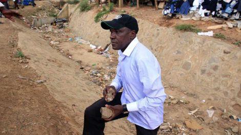 Former Kakamega Senator Boni Khalwale carries stones to defend himself in Kibera on November 7, 2019 during Kibra By-elections.