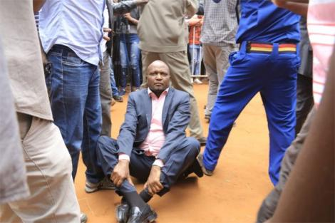 Police officers shielding Gatundu South MP Moses Kuria (seated) from bouncers who wanted to eject him from BBI rally in Kitui on February 1, 2020.