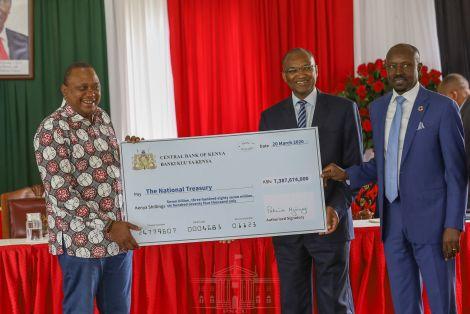 President Uhuru Kenyatta (left) accepting a contribution from CBK governor Patrick Njoroge, on March 20