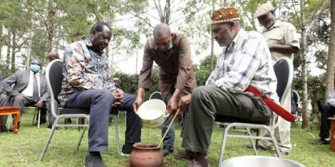 ODM leader Raila Odinga (left) and James Ngethe, a representative of the Council of Eminent Persons of Murang'a, conduct a ceremony