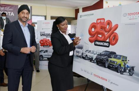 Co-op Bank Acting Director, Corporate and Institutional Banking Jackie Waithaka endorses the Toyota products display, witnessed by Toyota Kenya Managing Director Arvinder S. Reel at the launch of the joint financing deal that will offer up to 95% financing for the purchase of Toyota vehicles.
