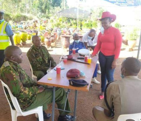 Woman shares food with officers manning the Muranga-Kiambu roadblock near Bluepost Delmonte/Delview area Thika Kiambu County.