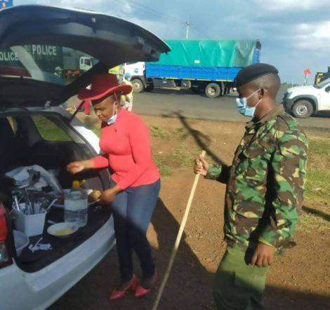 A woman shared her food with Police officers manning the Muranga-Kiambu roadblock near Bluepost Delmonte/Delview area Thika Kiambu County.