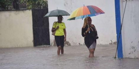 Mombasa residents walk through a flooded section on Nyerere Avenue following heavy rains on October 17, 2019.