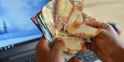 An image of a man holding a stash of cash