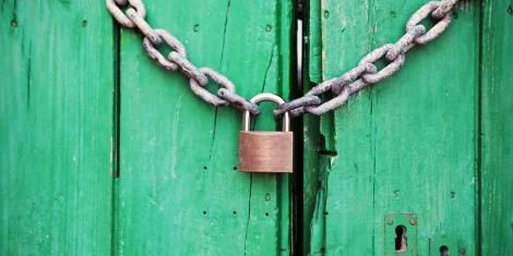 File image of a door locked with a chain link and a padlock.