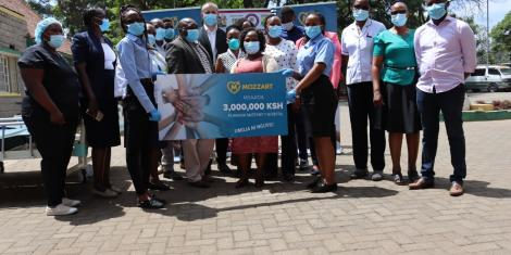 Pumwani Staff and Mozzart Bet team pose for a photo with the dummy cheque representing the sum of the donation.