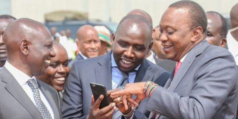 President Uhuru Kenyatta using a phone with Senator Kipchumba Murkomen as Deputy President William Ruto watches