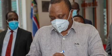 President Uhuru Kenyatta signing a ball after meeting with leaders from Western Kenya on July 1, 2020.
